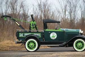 The 1930 Ford Model A Roadster pickup is a cool restoration Sinclair Tow Truck, complete with a Weaver crane and period-correct decals and pinstriped lettering in a forest green and lime green palette, with black and white accents.