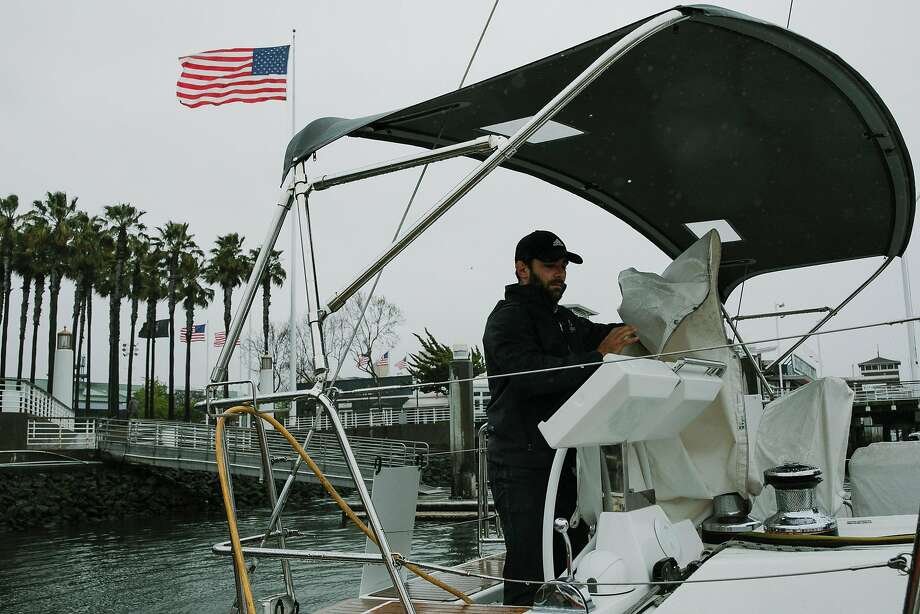 Billy Sarno of Passage Nautical removes the tarp on the control center of Beneteau Oceanis 55 in Oakland. Photo: Photos By Mason Trinca / Special To The Chronicle