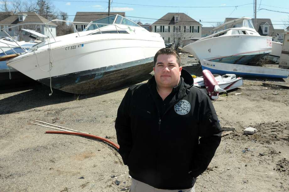 Bridgeport Harbormaster Ryan Conrad stands in a vacant lot where dozens of abandoned power boats from all over the city have been collected, in Bridgeport, Conn. April 5, 2018. Photo: Ned Gerard / Hearst Connecticut Media / Connecticut Post