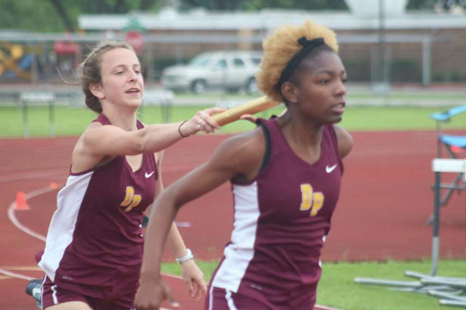 Deer Park's Camryn Masera hands the baton off to Amyre Ellis on the final exchange to the 4 by 100 relay race Thursday night. Although the team only scored four points, those four points proved pretty big since Deer Park's district title was by only 11 points. Photo: Robert Avery