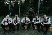 "A still from ""Super Troopers 2"": L-R: Writers and stars Kevin Heffernan, Steve Lemme, Jay Chandrasekhar, Paul Soter, and Erik Stolhanske, with a furry co-star."