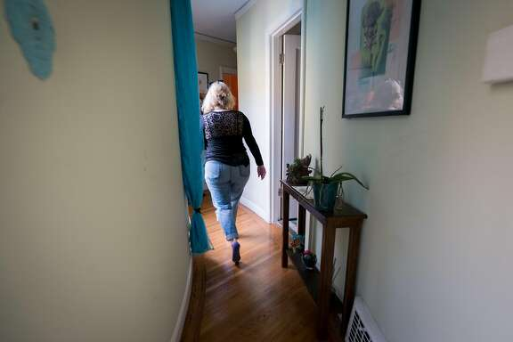 Leigh Anne Varney walks down the hallway of her home in the Outer Richmond district in San Francisco, Calif. on Friday, March 30, 2018.