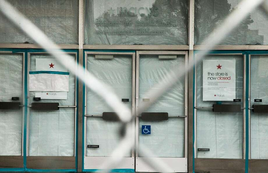 Large fences cover the shuttered doors of the former home of Macy's and future home of Whole Foods at Stonestown Galleria. Photo: Jessica Christian, The Chronicle