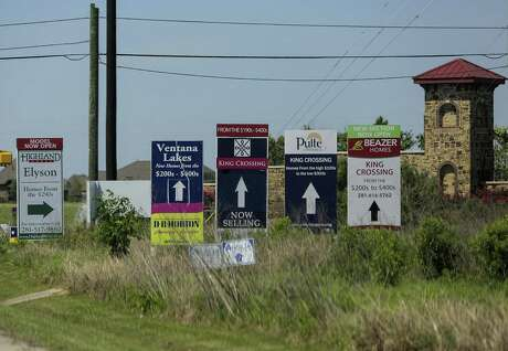 Builder signs for neighborhoods, including  Elyson, in northwest Harris County, photographed on Wednesday, April 4, 2018, in Katy. The developer avoided flood plain regulations by using dirt (fill) to raise the home sites above the level of the flood plain.( Elizabeth Conley / Houston Chronicle )