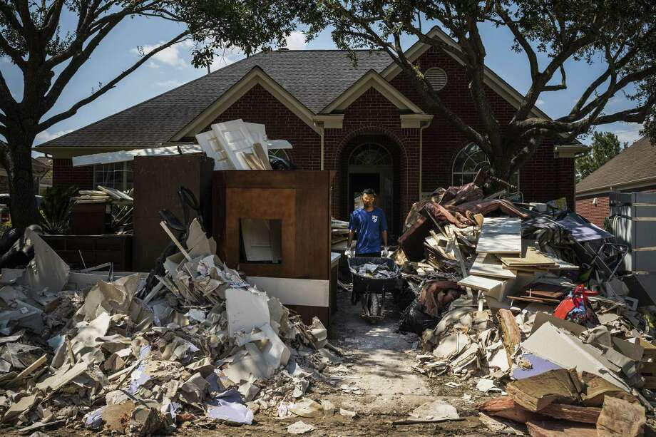 Miguel Lameda removes flood-damaged debris from a relative's home in the Canyon Gate at Cinco Ranch neighborhood of Houston, Sept. 10, 2017. The Texas suburb was intentionally flooded during Hurricane Harvey to save the city of Houston. Residents in the suburb are facing the brutal choice of whether to stay and face new floods or leave and sell their gutted homes at well below pre-storm prices. (Todd Heisler/The New York Times) Photo: TODD HEISLER, STF / NYT / NYTNS