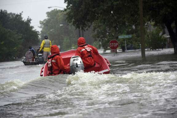 Coast Guard officials motor a boat along streets submerged in the floodwaters of Hurricane Harvey in 2017. The city of Friendswood will use $41 million approved by voters on Nov. 5 in a bond election to address drainage issues along Clear Creek.