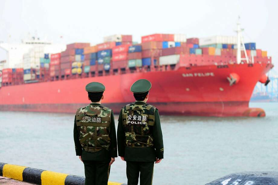 Chinese police officers watch a cargo ship at a port in eastern China. The escalating trade confrontation between Washington and Beijing hit global markets hard, sending the Dow Jones industrial average down more than 570 points. Photo: AFP / Getty Images