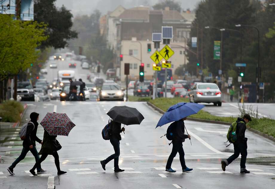 Pedestrians armed with umbrellas cross Oxford Street in Berkeley, Calif. on Friday, April 6, 2018. Photo: Paul Chinn / The Chronicle