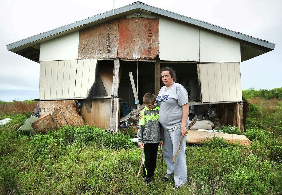 Charline Bearden, right, with her son Nicholas B. Kidd, 11, stand in front of their home that was lifted and floated about 200 yds from its original location where her new trailer sits. Many Rockport residents attend counseling session to help them deal with the stress that has stayed with them from Hurricane Harvey, on Wednesday, April 4, 2018.