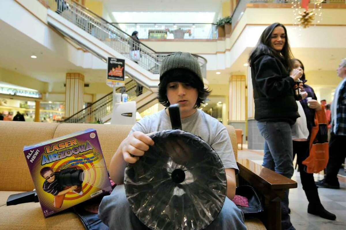Fifteen-year-old Andrew Iseman assemble a Laser Airzooka toy he bought at Spencers while out shopping Saturday with his mother Gina and sister Hannah at the Colonie Center in Colonie. (Michael P. Farrell/Albany Times Union)