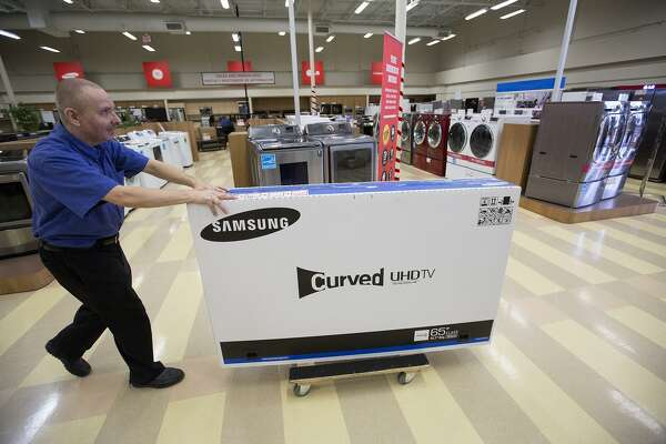 Bryan Jones wheels a television out to a customer at Conn's, Friday, Nov. 27, 2015, in Baytown. (Cody Duty / Houston Chronicle)