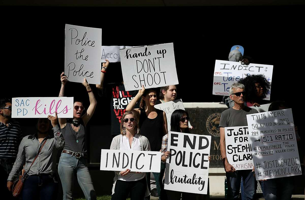 Black Lives Matter protesters hold signs as they stage a demonstration outside of office of Sacramento district attorney Anne Schubert on March 29, 2018 in Sacramento, California. Hours after the funeral for Stephon Clark, doze