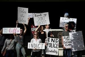 SACRAMENTO, CA - MARCH 29:  Black Lives Matter protesters hold signs as they stage a demonstration outside of office of Sacramento district attorney Anne Schubert on March 29, 2018 in Sacramento, California. Hours after the funeral for Stephon Clark, doze