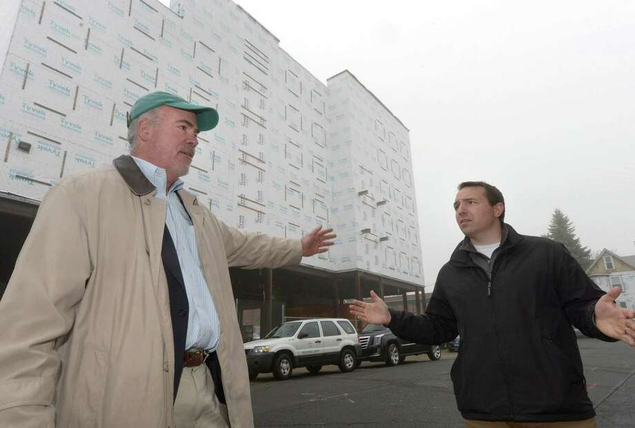 The newly formed Wall Street Neighborhood Association including Michael McGuire, Principal Austin McGuire Company, and Jason Milligan, founder Milligan Realty,  give a walking tour of Wall Street Wednesday, April 4, 2018, outlining its hopes for what had been the city's historic downtown prior to the 1955 flood and whose redevelopment is looking a little shaky after the POKO development stalled, Wall Street Theater filed for bankruptcy and rehabilitation of the fire-damaged building at 45 Wall St. crawls along in Norwalk, Conn. Photo: Erik Trautmann / Hearst Connecticut Media / Norwalk Hour