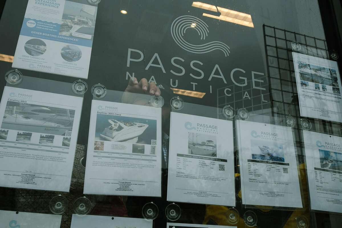 Billy Sarno of Passage Nautical straightens out the listings on their windows of Passage Nautical's office in Oakland, Calif., Friday, April 6, 2018.