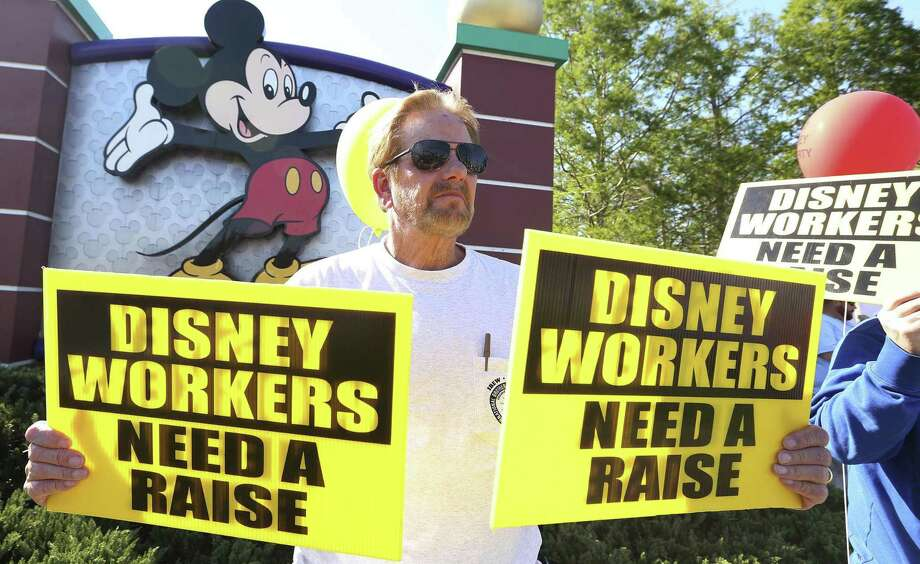 Larry Kidd holds signs in front of Walt Disney World hotel property during a protest last month  in Orlando, Fla. Photo: Stephen M. Dowell, MBO / Associated Press / Orlando Sentinel 2018