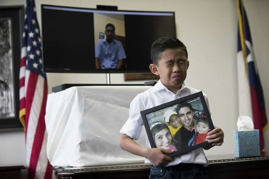 Walter Escobar, 8, becomes emotional as he holds a photo of his family and his father Jose Escobar live on video chat  on the background during a press conference on which Congressman Al Green (TX-09) announces a plan to introduce The Reentry and Reunification Act of 2018, Friday, April 6, 2018, in Houston. ( Marie D. De Jesus / Houston Chronicle ) Photo: Marie D. De Jesus, Houston Chronicle / Houston Chronicle / © 2018 Houston Chronicle