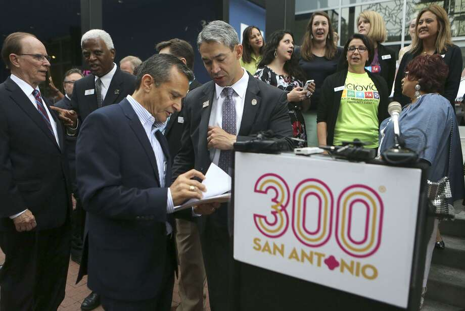San Antonio Assistant City Manager Carlos Contreras (left, foreground) and San Antonio Mayor Ron Nirenberg (right, foreground) coordinate before making an announcement at Market Square about the Tricentennial Commemorative Week lineup of events. Photo: John Davenport /San Antonio Express-News / ©John Davenport/San Antonio Express-News