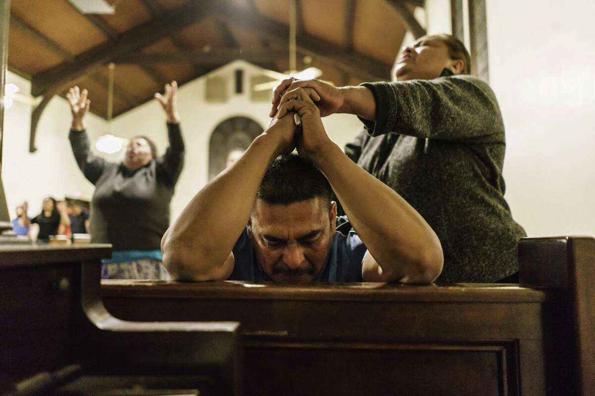 Jesus Aceves, center, who was detained by Immigration and Customs Enforcement agents but was released on bond, awaiting a hearing before an immigration judge, prays at his brother's church El Aposento Alto on March 7, 2018 in Wasco, Calif.