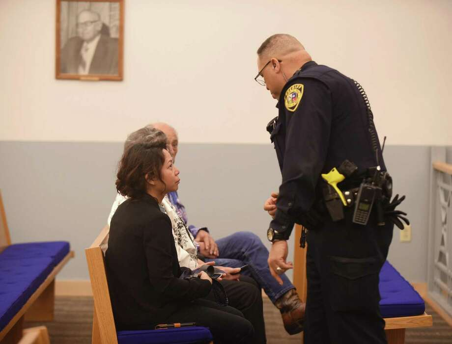 Linda Benavides, who is the wife of Mark Benavides, receives his belt and necktie Friday from a sheriff's deputy after he was sentenced to 80 years as punishment after being convicted for continuous trafficking of persons. Photo: Billy Calzada /San Antonio Express-News / San Antonio Express-News