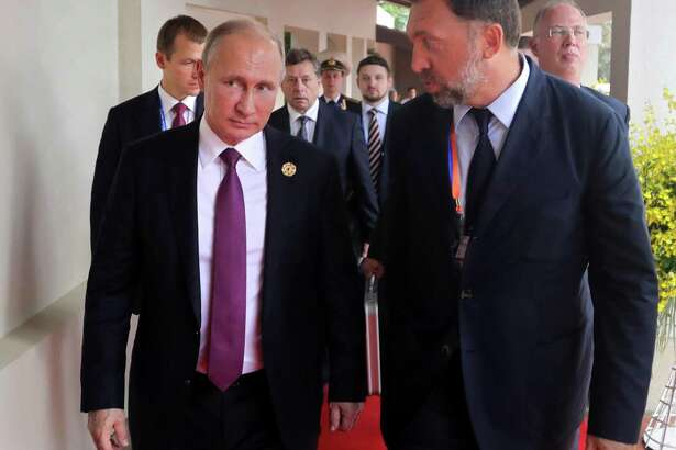 Russia's President Vladimir Putin, left, and Russian metals magnate Oleg Deripaska, right, walking to attend the APEC Business Advisory Council dialogue in Danang, Vietnam. The United States punished dozens of Russian oligarchs and government officials on Friday, April 6, 2018, with sanctions that took direct aim at President Putin's inner circle, as President Donald Trump's administration tried to show he's not afraid to take tough action against Moscow. Seven Russian tycoons, including aluminum magnate Deripaska, were targeted, along with 17 officials and a dozen Russian companies, the Treasury Department said.