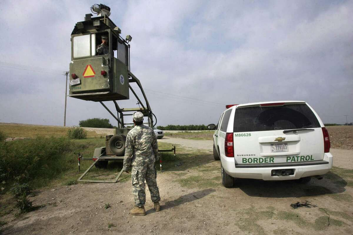FILE - In this April 19, 2011 file photo, a member of the U.S. National Guard checks on his colleague inside a Border Patrol Skybox near the Hidalgo International Bridge in Hidalgo, Texas.