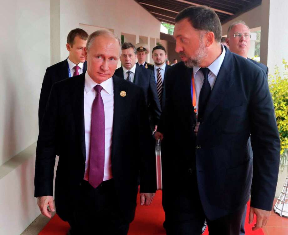 File-This Nov. 10, 2017, file photo shows Russia's President Vladimir Putin, left, and Russian metals magnate Oleg Deripaska, right, walking to attend the APEC Business Advisory Council dialogue in Danang, Vietnam. The United States punished dozens of Russian oligarchs and government officials on Friday, April 6, 2018, with sanctions that took direct aim at President Putin's inner circle, as President Donald Trump's administration tried to show he's not afraid to take tough action against Moscow. Seven Russian tycoons, including aluminum magnate Deripaska, were targeted, along with 17 officials and a dozen Russian companies, the Treasury Department said.  (Mikhail Klimentyev, Sputnik, Kremlin Pool Photo via AP, File) Photo: Mikhail Klimentyev / POOL SPUTNIK KREMLIN