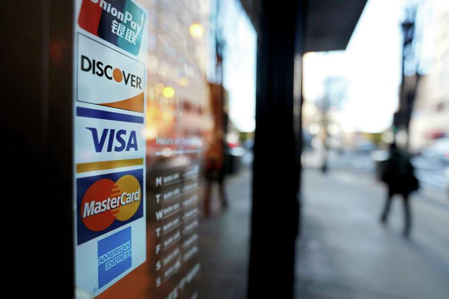 Credit card logos are posted to the door of a business in Atlanta. The Federal Reserve said Friday that consumer borrowing rose $10.6 billion in March to nearly $3.9 trillion. Photo: David Goldman, STF / Associated Press / Copyright 2018 The Associated Press. All rights reserved.
