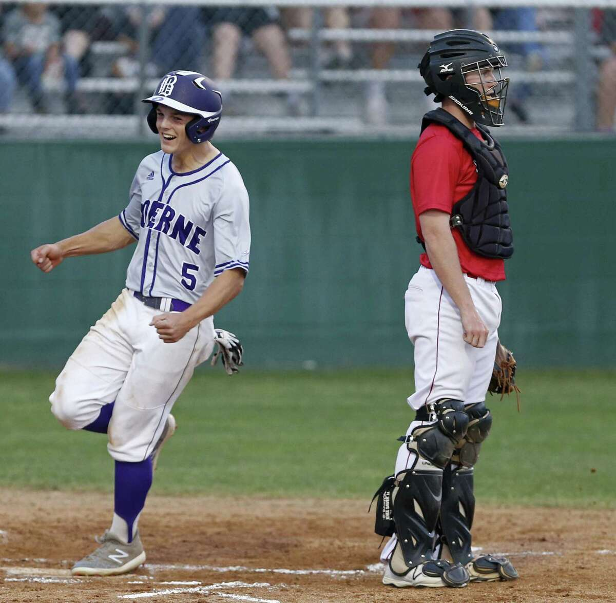 Boerne's Douglas Hodo celebrates as he scores around Fredericksburg's Daylon Nebgen during the second inning Friday April 6, 2018 at Greyhound Field in Boerne, Tx.