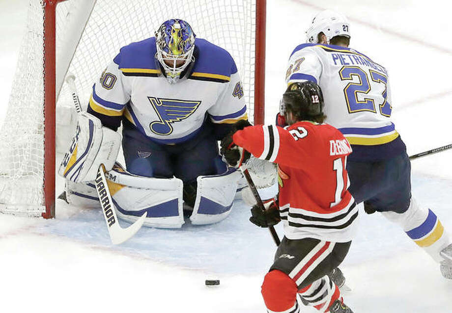 Blues goalie Carter Hutton, left, blocks a shot by Chicago's Alex DeBrincat (12) during the first period of Friday night's game in Chicago. Photo: AP