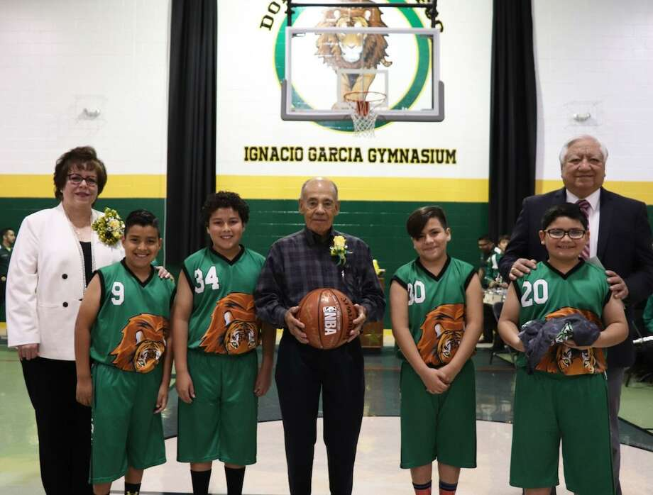 LISD Superintendent Dr. Sylvia Rios, left, and LISD Vice President Hector Noyola, right, join Mr. Ignacio Garcia, center, with members of the Gallego basketball team, who take the first shots in the newly named Ignacio Garcia Gymnasium. Photo: Courtesy Of LISD