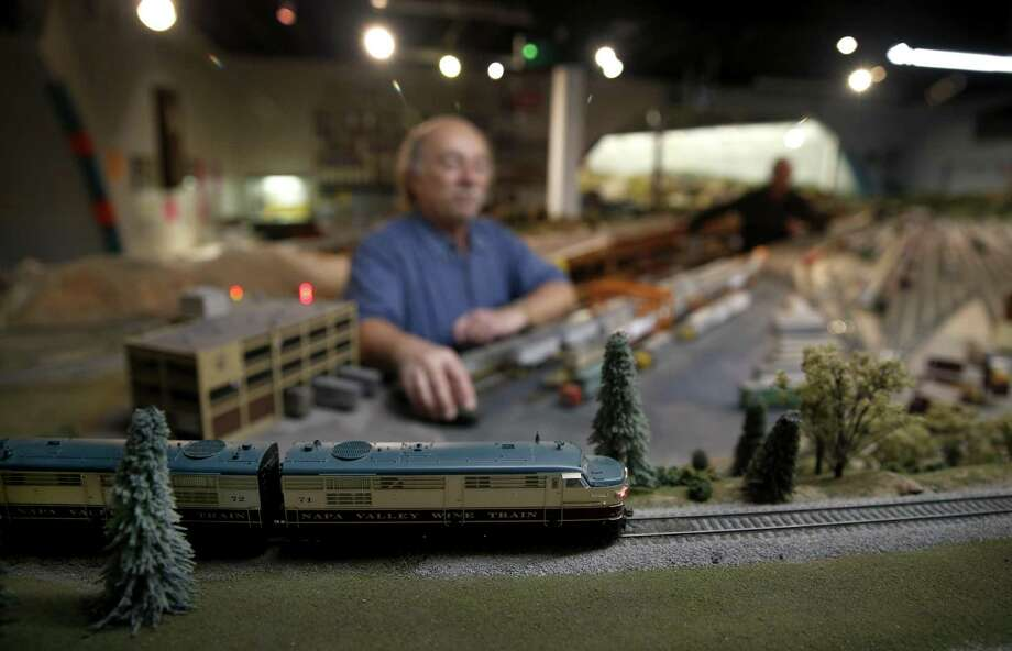 An HO scale train rolls past Wayne Monger while he cleans a section of track at the model railroad layout. Photo: Photos By Paul Chinn / The Chronicle / ONLINE_YES