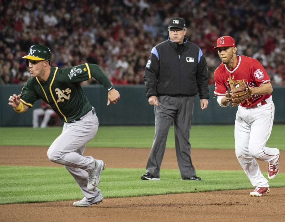The A's Boog Powell gets caught in a rundown by Los Angeles' Andrelton Simmons during the fourth inning. Photo: Kyusung Gong / Associated Press / AP