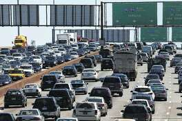 Traffic begins to thicken as motorists getting an early jump to Memorial Day destinations in Indiana and Michigan travel an interstate freeway through Chicago in 2014.