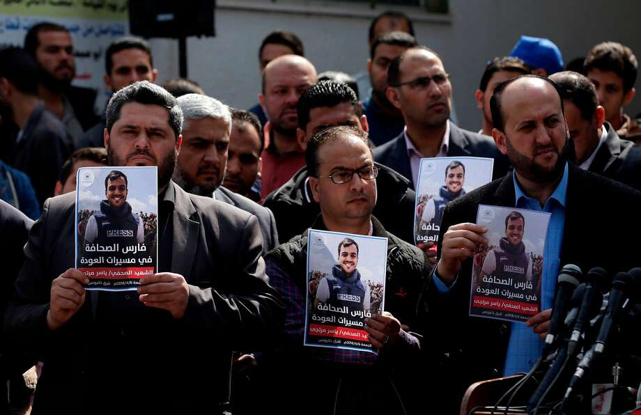 Palestinian journalists carry a photo of journalist Yasser Murtaja during his funeral in Gaza City. Photo: Mahmud Hams / AFP / Getty Images