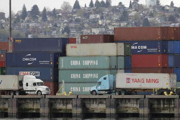 """Trucks pass by cargo containers labeled """"China Shipping,"""" Friday, April 6, 2018, at the Port of Seattle. On Thursday, President Donald Trump ordered the government to consider a bigger set of tariffs on goods imported from China. (AP Photo/Ted S. Warren)"""
