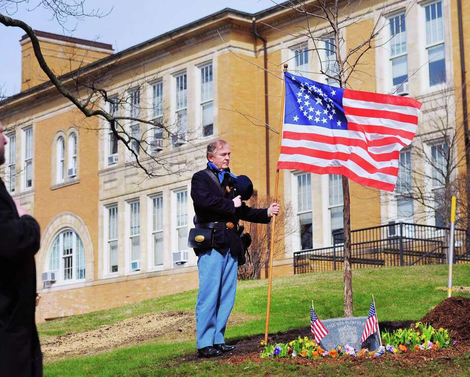 Holding a historical American Flag, David Wold of Greenwich wore a Union Army uniform and removed his hat while standing by the new white oak tree during the rededication of the Grand Army of the Republic Civil War Veterans Memorial in front of the Havemeyer Building in Greenwich, Conn., Saturday morning, April 7, 2018. A white oak tree was replanted as part of the ceremony that was put together by the Greenwich Veterans Council in cooperation with the Greenwich Historical Society to honor those Greenwich citizens who served and those died in the American Civil War. The original white oak at the memorial that was planted on April 9, 1914, marking the anniversary of the Confederacy's surrender at Appomattox, was replaced with a new tree. Officials said the original tree was diseased and recently cut-down. Photo: Bob Luckey Jr. / Hearst Connecticut Media / Greenwich Time