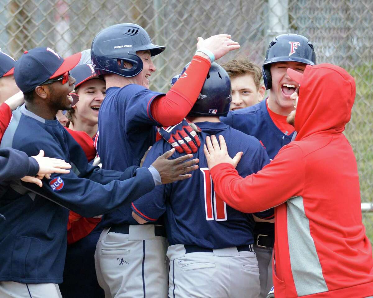 Foran players celebrate a run scored by teammate Kevin Lanese (#11) during the high school baseball game between Stamford High School and Foran High School at Stamford High School, Conn., Saturday, April 7, 2018. Foran won the game 8-5 over Stamford.