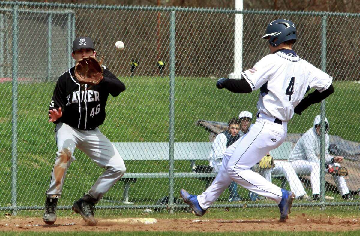 Xavier third baseman Connor Cardi receives the ball to get the out on Staples' Max Popken during baseball action in Westport, Conn., on Saturday Apr. 7, 2018.