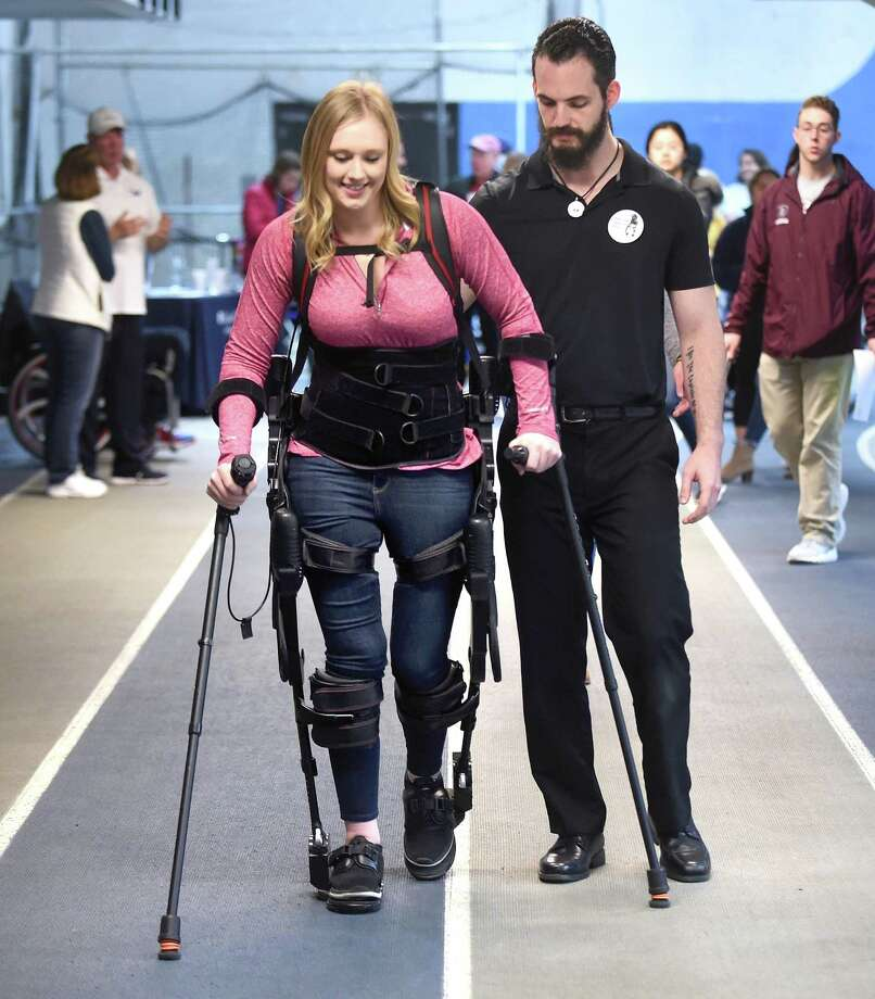 Jillian Harpin gives a demonstration of an Ekso Bionics exoskeleton with the assistance of Gaylord Hospital physical therapist Tim Kilbride during the Adaptive Sports Fest at Southern Connecticut State University's Moore Field House in New Haven on Saturday. Photo: Arnold Gold / Hearst Connecticut Media / New Haven Register