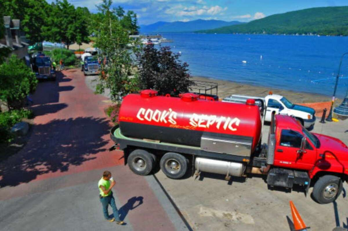 In this file photo from July 2009, workers clear sewage from a spill at a pump house on the closed Shepard Park beach in the village of Lake George. A year later, the water is clean and ready for swimmers and opens officially June 24. ( Philip Kamrass / Times Union)