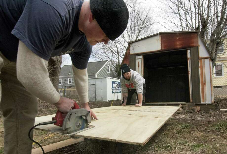 Veterans Chris Robinson, left, and Jonathan Minkler, work together to repair a storage shed at the home of Vietnam veteran Peter Falcione in Milford, Conn., on Saturday Apr. 7, 2018. The vets were part of a team of House of Heroes Connecticut (HOHCT) volunteers who descended upon Falcione's home to execute a wide variety of repairs and renovations to make his home safer and more accessible. Photo: Christian Abraham / Hearst Connecticut Media / Connecticut Post