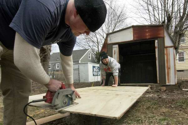 Veterans Chris Robinson, left, and Jonathan Minkler, work together to repair a storage shed at the home of Vietnam veteran Peter Falcione in Milford, Conn., on Saturday Apr. 7, 2018. The vets were part of a team of House of Heroes Connecticut (HOHCT) volunteers who descended upon Falcione's home to execute a wide variety of repairs and renovations to make his home safer and more accessible.