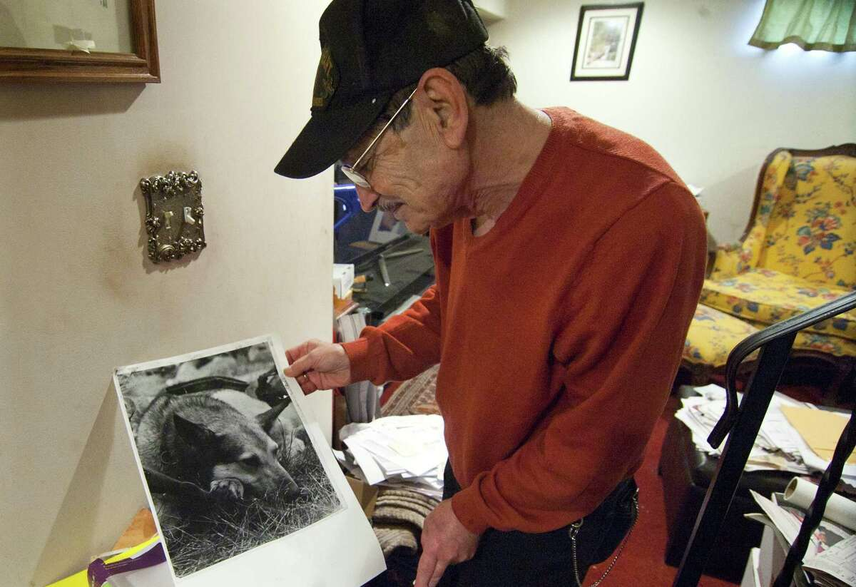 Vietnam veteran Peter Falcione pauses to show a photo of Shannon, the K9 he handled on patrols during his time in the war, while at his home in Milford, Conn., on Saturday Apr. 7, 2018. A team of House of Heroes Connecticut (HOHCT) volunteers descended upon Falcione's home to execute a wide variety of repairs and renovations to make his home safer and more accessible. Up to 15 of those volunteers were members of The Honorable W. Patrick Donlin Assembly #2459 of the Knights of Columbus, which partnered with HOHCT as a project sponsor.