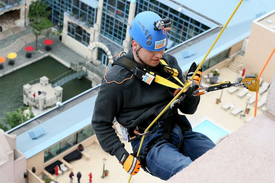 """Junior Orozco, a Boysville resident, begins to rappel from the 19th floor of the Marriott Rivercenter, 100 Bowie St. in Boysville's """"Over the Edge"""" fundraising event on Saturday, April 7, 2018. MARVIN PFEIFFER/mpfeiffer@express-news.net Photo: Marvin Pfeiffer /San Antonio Express-News / Express-News 2018"""