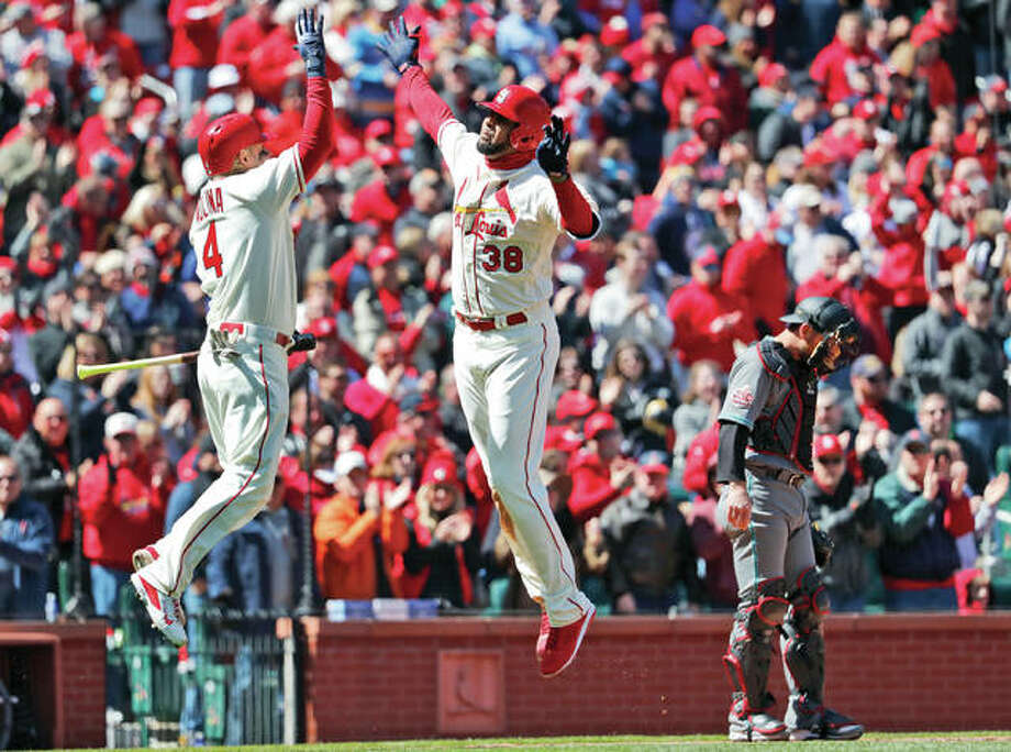 The Cardinals' Jose Martinez (38) is congratulated by teammate Yadier Molina (left) after hitting a three-run home run as Diamondbacks catcher Jeff Mathis stands by during the third inning Saturday at Busch Stadium. Photo: Associated Press