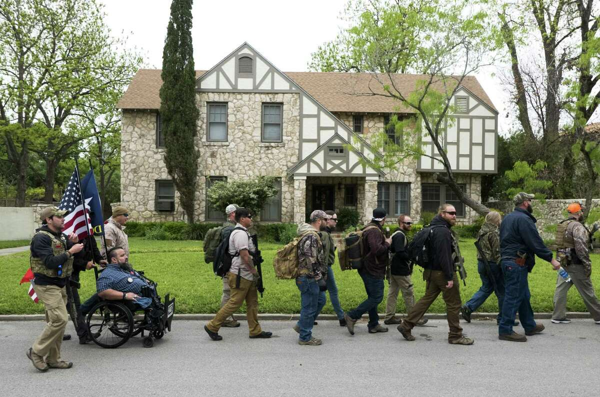 Members of Open Carry Texas and their supporters march through Olmos Park on Saturday, April 7, 2018. They were demanding that police chief Rene Valenciano lose his job over what they say is unfair treatment of their members.
