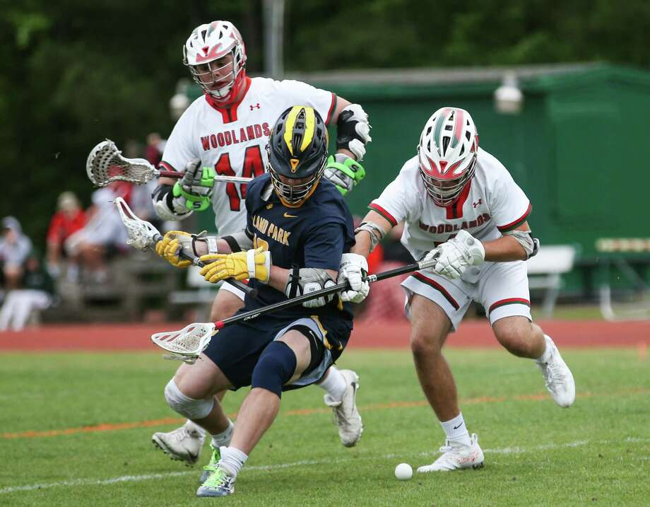The Woodlands' Diego Zimmerman (4) and Nathan Drickamer (14) battle for possession of the ball with Highland Park's Cameron Reeves (18) during the lacrosse game on Saturday, April 7, 2018, at The Woodlands High School. (Michael Minasi / Houston Chronicle) Photo: Michael Minasi, Staff Photographer / © 2018 Houston Chronicle