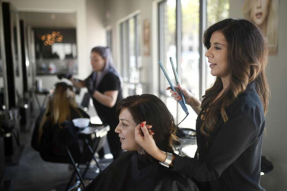 Chrissy Hale, owner of Halo Hair and Beauty Bar, works with a client on April 7, 2018. Hale is awaiting word on when hair salons can reopen.