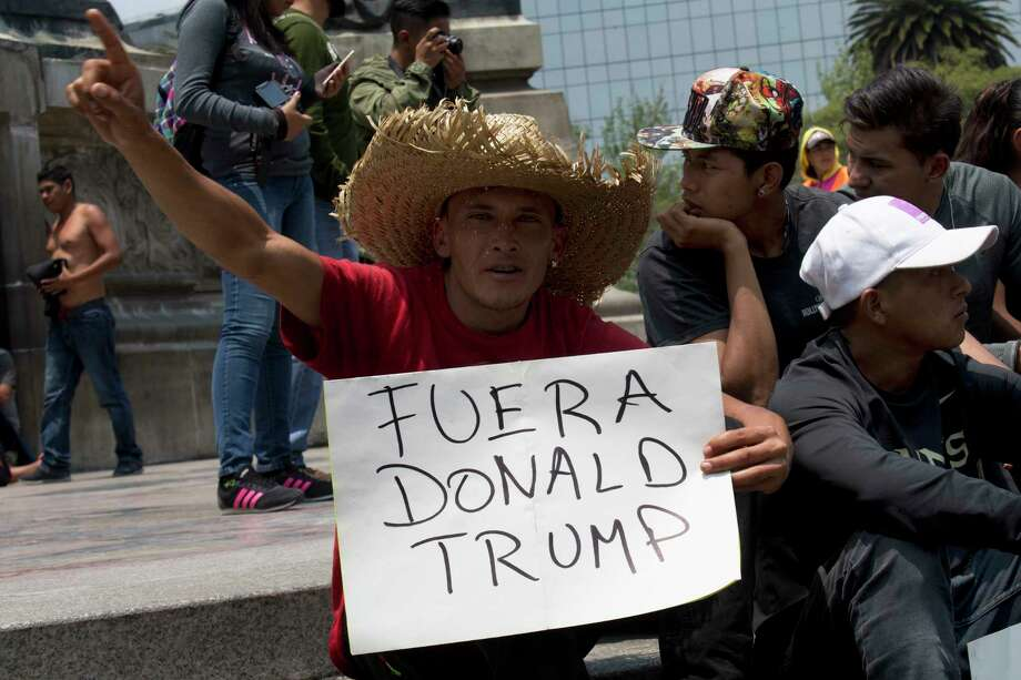 "A Central American migrant, part of the the annual Stations of the Cross caravan march for migrants' rights, holds a sign that reads in Spanish ""Out with Donald Trump"" during a protest at the Angel of Independence monument in Mexico City, Saturday, April 7, 2018. Mexico's capital is the final planned stop of the migrant caravan that left from the Mexico-Guatemala border late last month to draw attention to policies toward immigrants and refugees. (AP Photo/Marco Ugarte) Photo: Marco Ugarte / Copyright 2018 The Associated Press. All rights reserved."